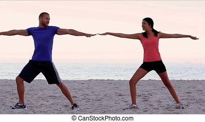 Friends stretching on the beach together