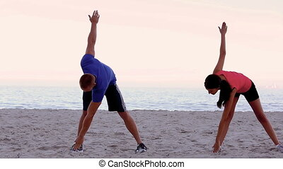 Friends stretching together on the beach