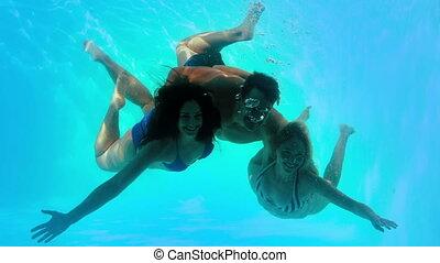 Friends swimming underwater in pool