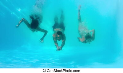 Friends swimming underwater in pool