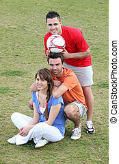 Friends taking a break from playing football