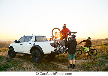 Friends Taking MTB Bikes off the Pickup Offroad Truck in Mountains at Sunset. Adventure and Travel Concept.