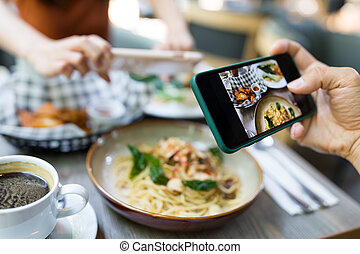 Friends taking photo on dish in restaurant
