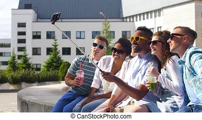 friends taking picture by on selfie stick in city -...