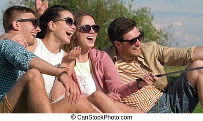 friends taking picture by selfie stick at seaside -...