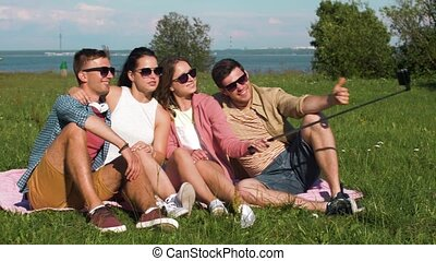 friends taking picture by selfie stick in summer