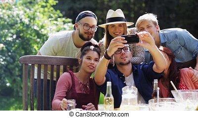 friends taking selfie at party in summer garden