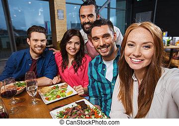 friends taking selfie by smartphone at restaurant - leisure,...