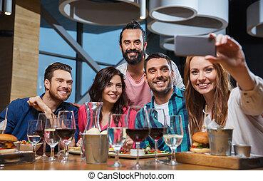 friends taking selfie by smartphone at restaurant -...