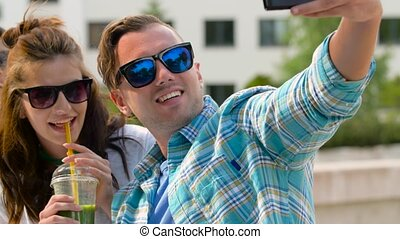 friends taking selfie by smartphone in city