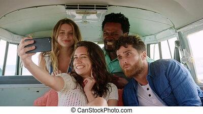 Friends taking selfie in camper van at beach 4k - Front view...