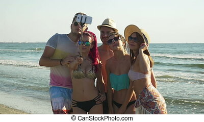 Friends taking selfie on a beach in summertime