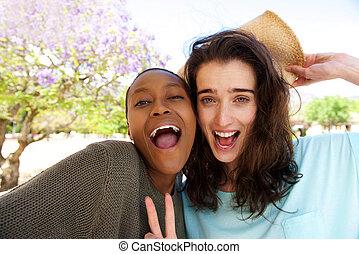 Friends taking selfie portrait outdoors