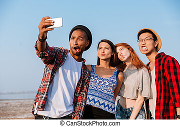Friends taking selfie with cell phone and making funny faces