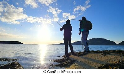 Friends talk about fishing and health. Young working fisherman on stone at sea level. Hiker man with medicine crutches and leg in functional knee braces. 