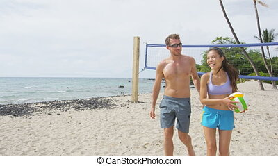 Friends talking after beach volleyball active fun living sporty active lifestyle. Portrait of people walking with volley ball after game in summer. Woman and man fitness model doing sport on beach.