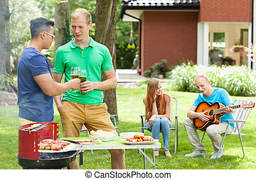 Friends talking on a garden party, horizontal