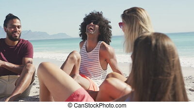 Friends talking seaside - Front view of a multi-ethnic group...