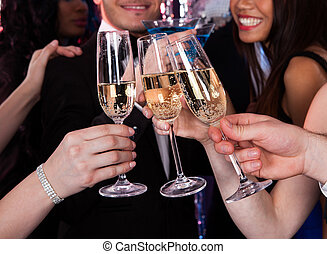 Cropped image of friends toasting champagne flutes at nightclub