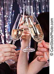 Friends Toasting Champagne At Nightclub - Cropped image of...