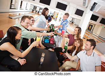 Friends Toasting Drinks in Bowling Club - Group of young...