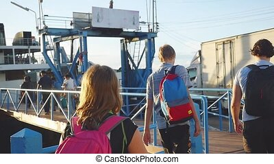 Friends Travelers with backpack are walking on pier to the...