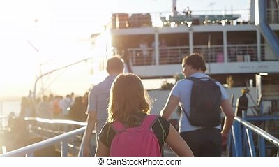 Friends Travelers with backpack are walking on pier to the ferry in slow motion during beautiful sunset with lens flare effects. 1920x1080