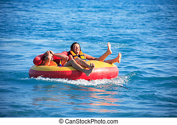 Laughing teenage boy and girl in inner tube after driving