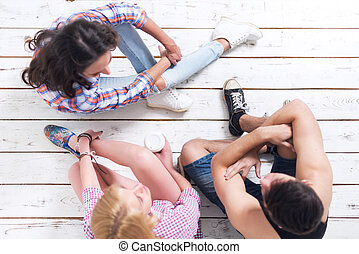 Friends two girls and guy sitting on floor in summer jeanswear street urban casual style talking, having fun, top view