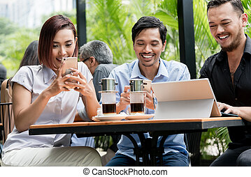 Friends using devices connected to the wireless internet of a modern coffee shop