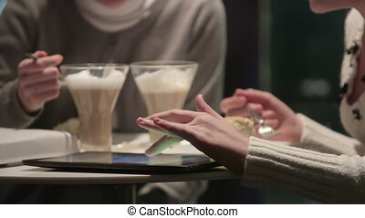 Friends using digital tablet computer at night coffee shop close-up