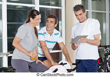 Friends Using Digital Tablet In Gym