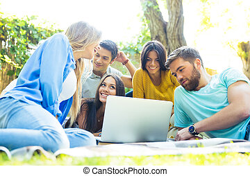 Friends using laptop together outdoors - Happy friends using...