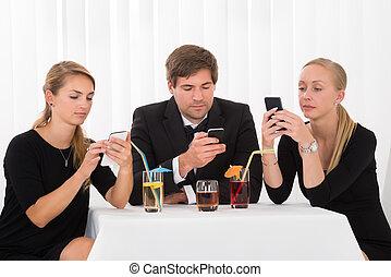 Friends Using Mobile Phones In Restaurant
