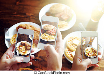 friends using smartphones to take photos of food with...