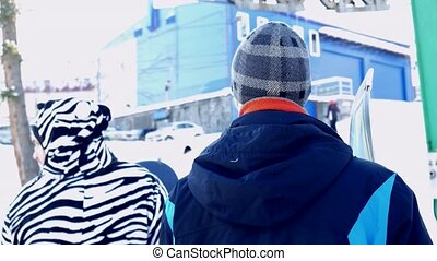 Friends wait and go on in line to the ski lift at the ski...