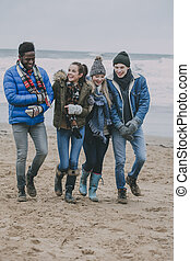 Friends Walking Along A Winter Beach - A group of friends...