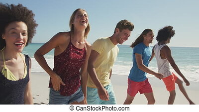 Friends walking seaside - Side view of a multi-ethnic group ...