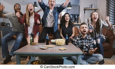 Friends watch sports on TV, celebrate success. Crazy...