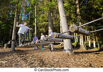 Friends Watching Man Crossing Log Bridge In Forest