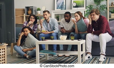 Friends watching sad movie on TV crying and eating snacks together at home
