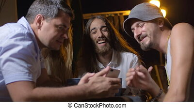 Friends watching something on smartphone and laughing at the party