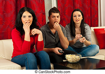 Friends watching tv and eating popcorns