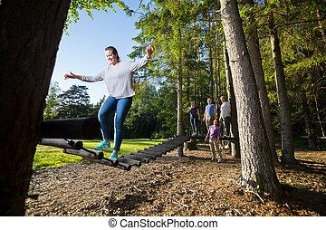 Friends Watching Woman Crossing Log Bridge In Forest -...