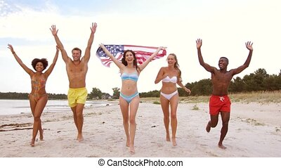 friends with american flag running on summer beach -...