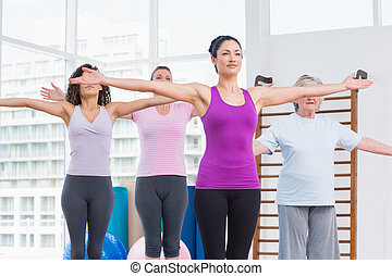 Friends with arms outstretched exercising in gym