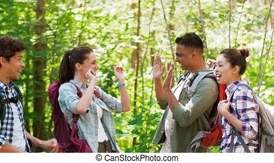 friends with backpacks hiking and making high five - travel,...