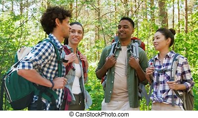 friends with backpacks on hike talking in forest - travel, ...