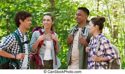 friends with backpacks on hike talking in forest