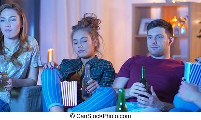 friends with beer and popcorn watching tv at home -...